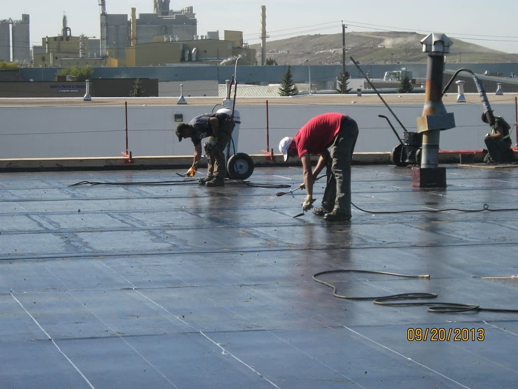 roofing works being carried out on a commercial flat roof